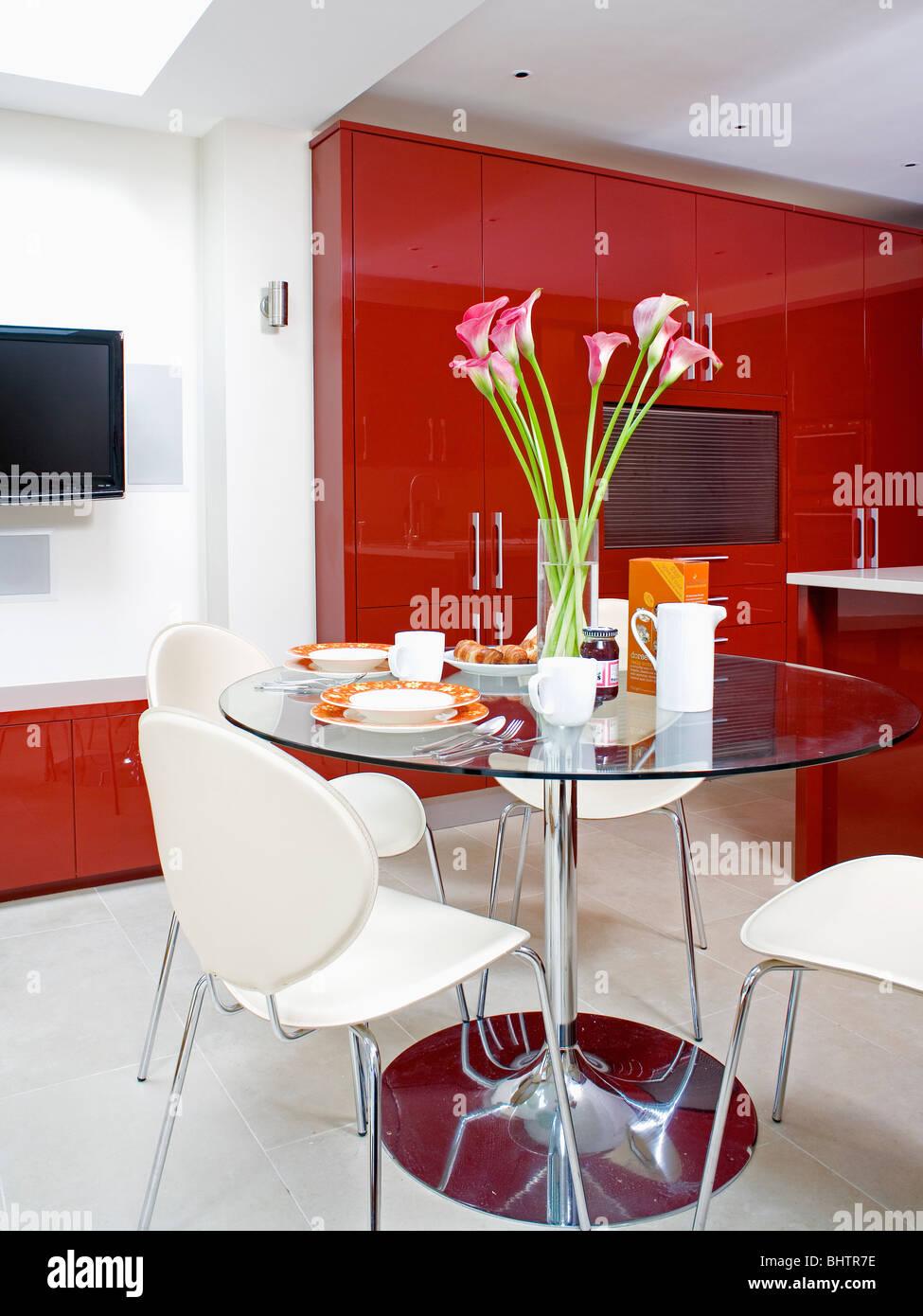 Weiße Stühle Am Runden Glas Und Stahl Tisch In Moderne Küche Esszimmer Mit  Weißer Bodenbelag Und Rotem Lack Schränke