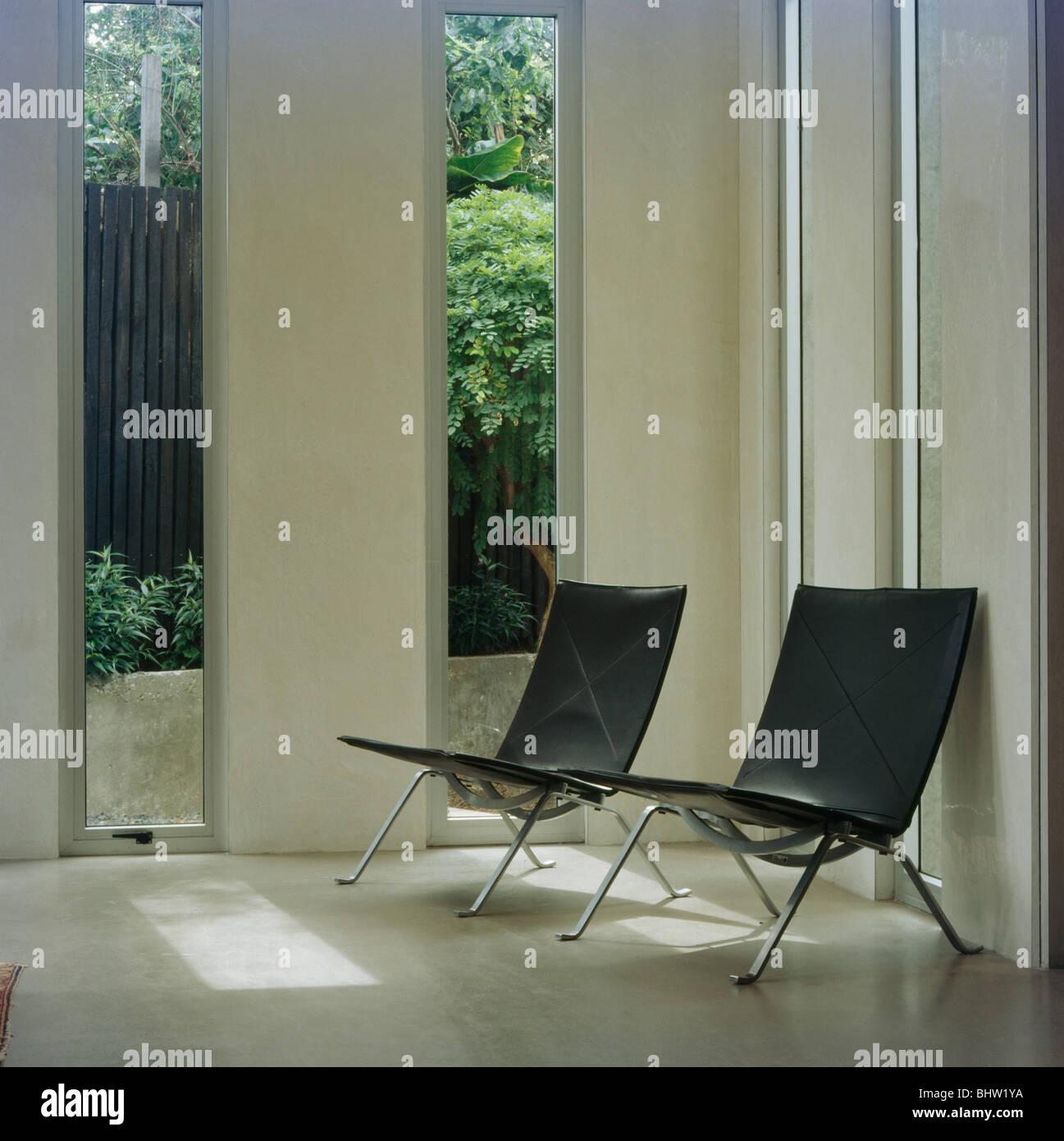 Schwarzes Leder Und Chrom Stühlen Vor Hohen Schmalen Fenstern In Moderne  Wohnzimmer
