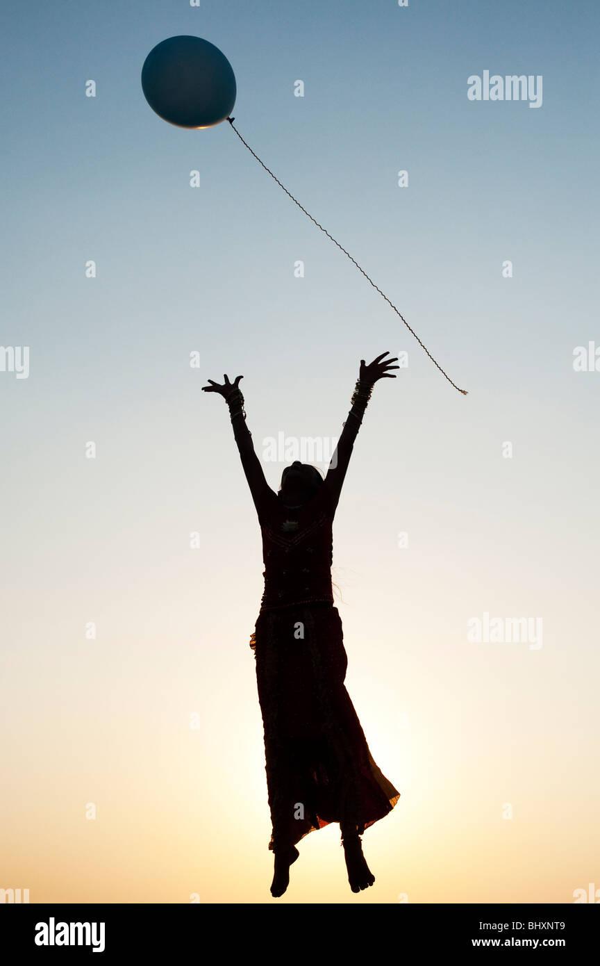 Silhouette von einem jungen indischen Mädchen spielen mit einem Ballon bei Sonnenuntergang. Indien Stockbild