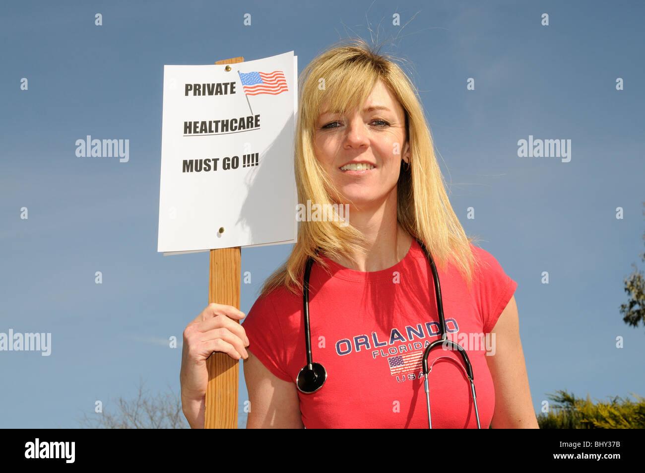 Private Gesundheitsvorsorge in den USA muss weibliche Demonstrant rotes Hemd trägt und hält ein Stethoskop Stockbild