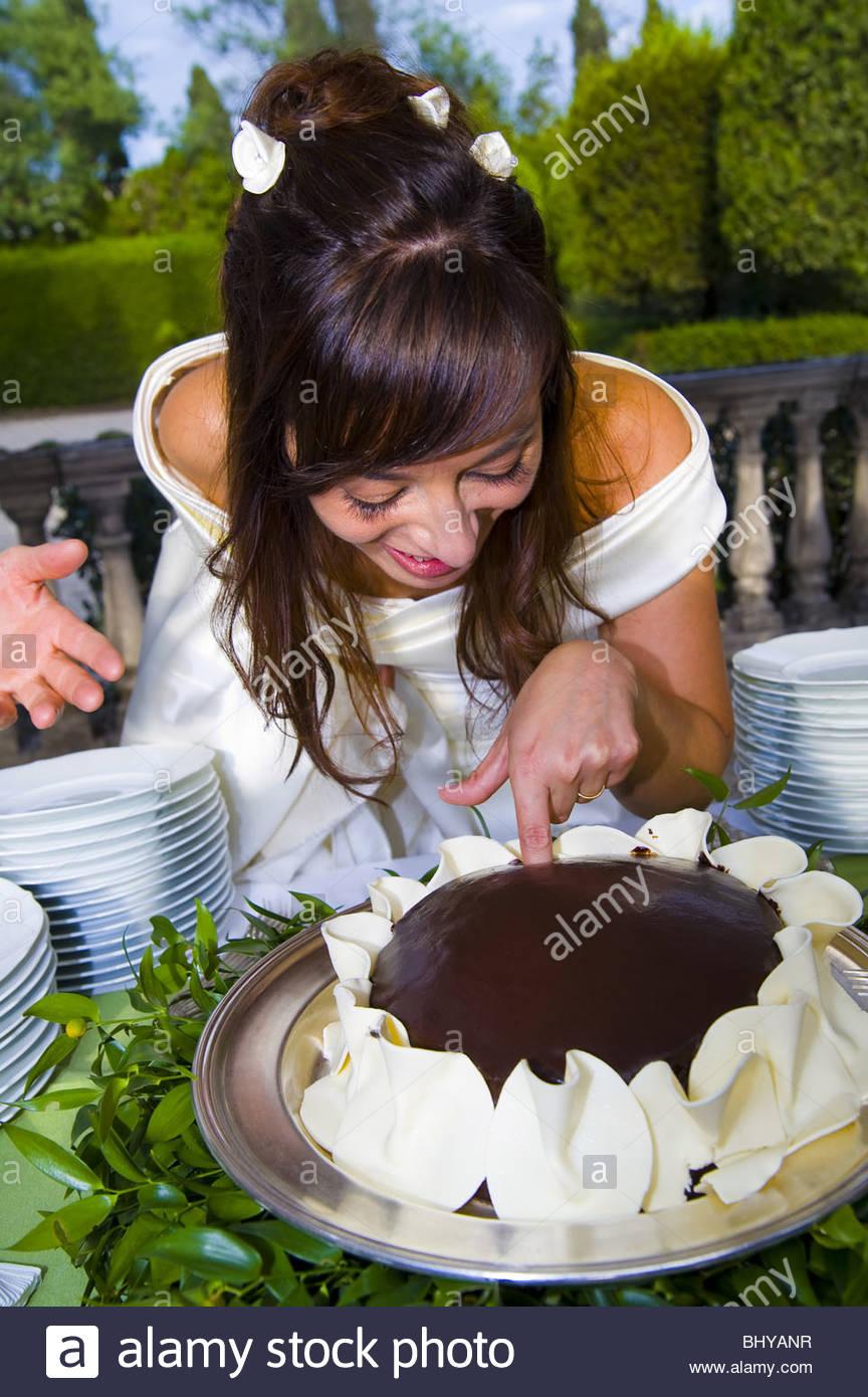 Braut, Finger in eine Schokolade Hochzeitstorte Stockbild