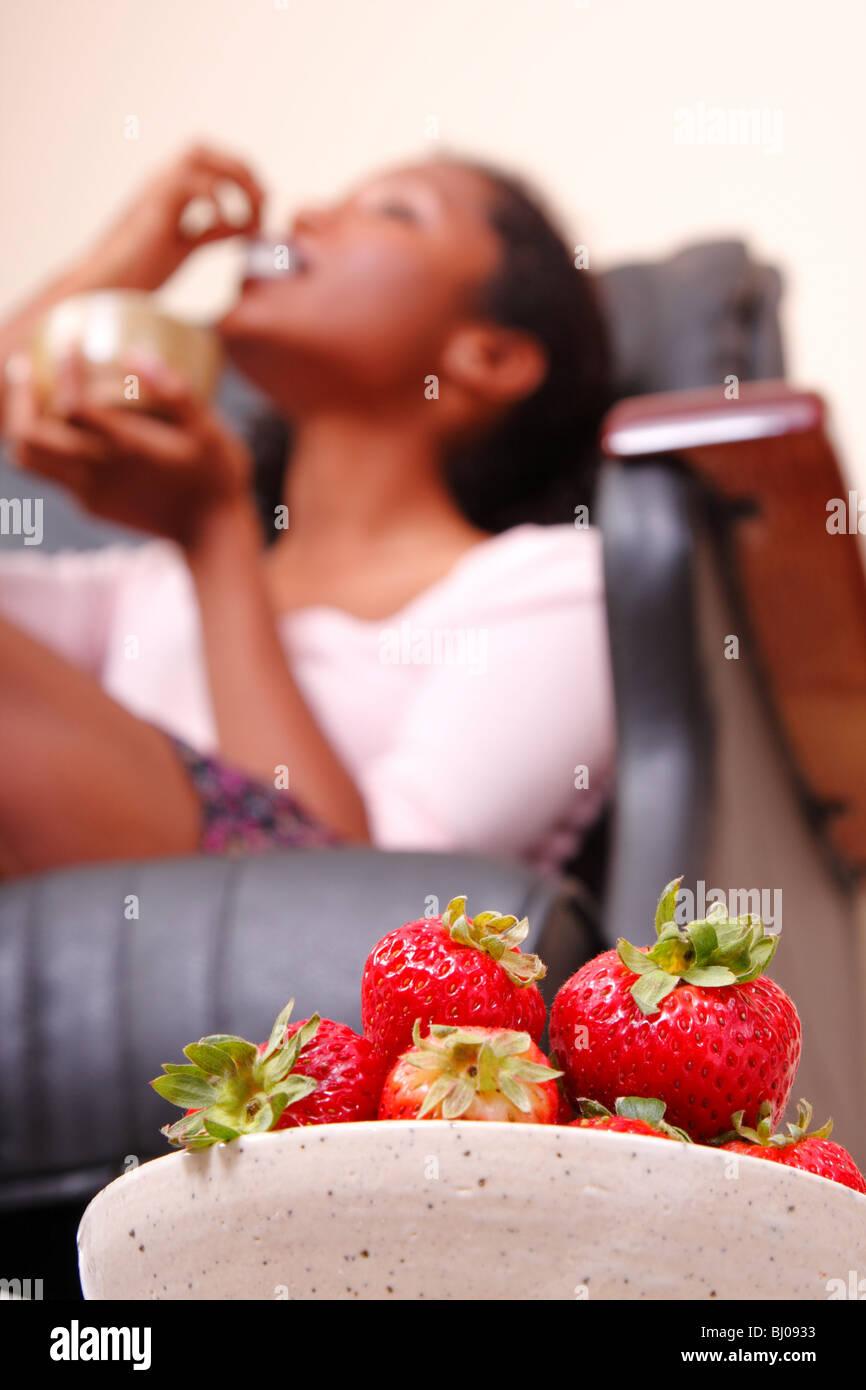 Eine Frau Essen Erdbeeren In Einem Stuhl Massagepediküre Stockfoto