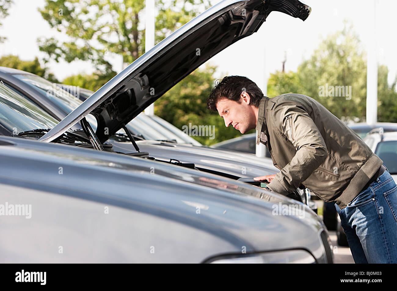 Mann an Kfz-Händler prüfen Motor Autos Stockbild