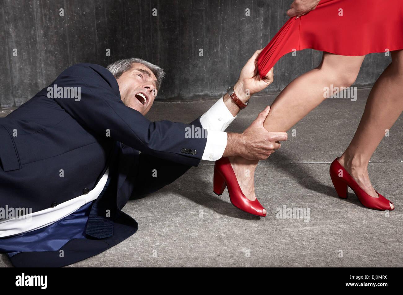 verzweifelter Mann auf Boden versucht, Frau halten Stockbild