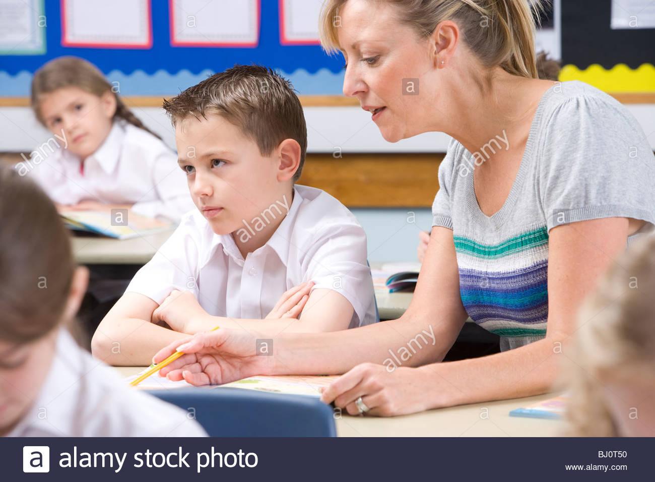 Lehrer helfen, hartnäckige Student mit Studien im Klassenzimmer Stockbild