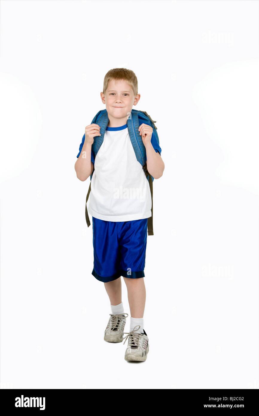 Ein glückliches Kind mit einem Rucksack geht in Richtung der Kamera Stockbild