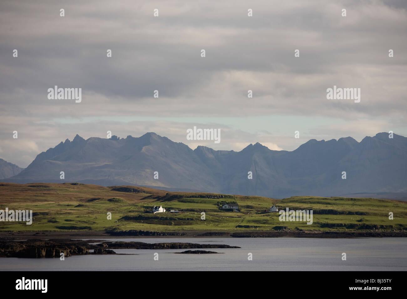 In den ruhigen Gewässern des schottischen Bucht sitzen einzelne Häuser und Crofts vor den dramatischen Stockbild