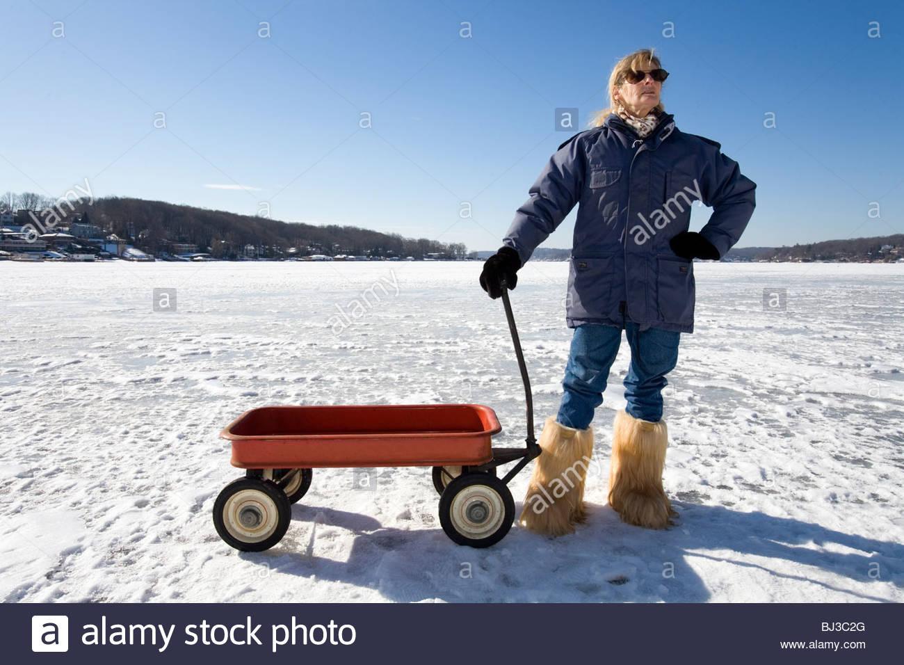Frau steht neben ihr Radio Flyer Red Wagon auf zugefrorenen See im Winter. Stockfoto