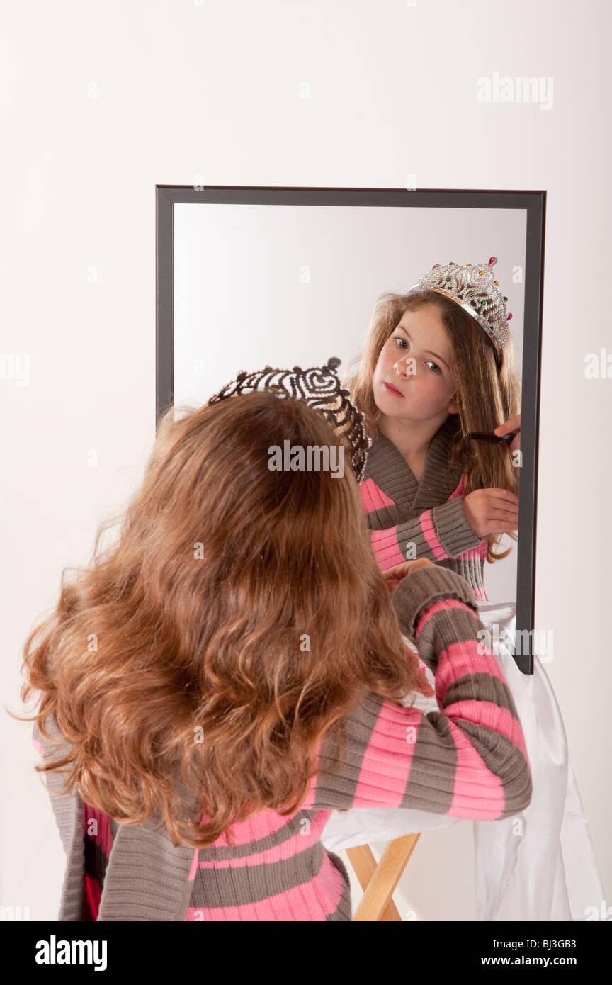 kleines Mädchen betrachtet sich im Spiegel während des Spielens Make-up und Märchen Prinzessin Stockbild