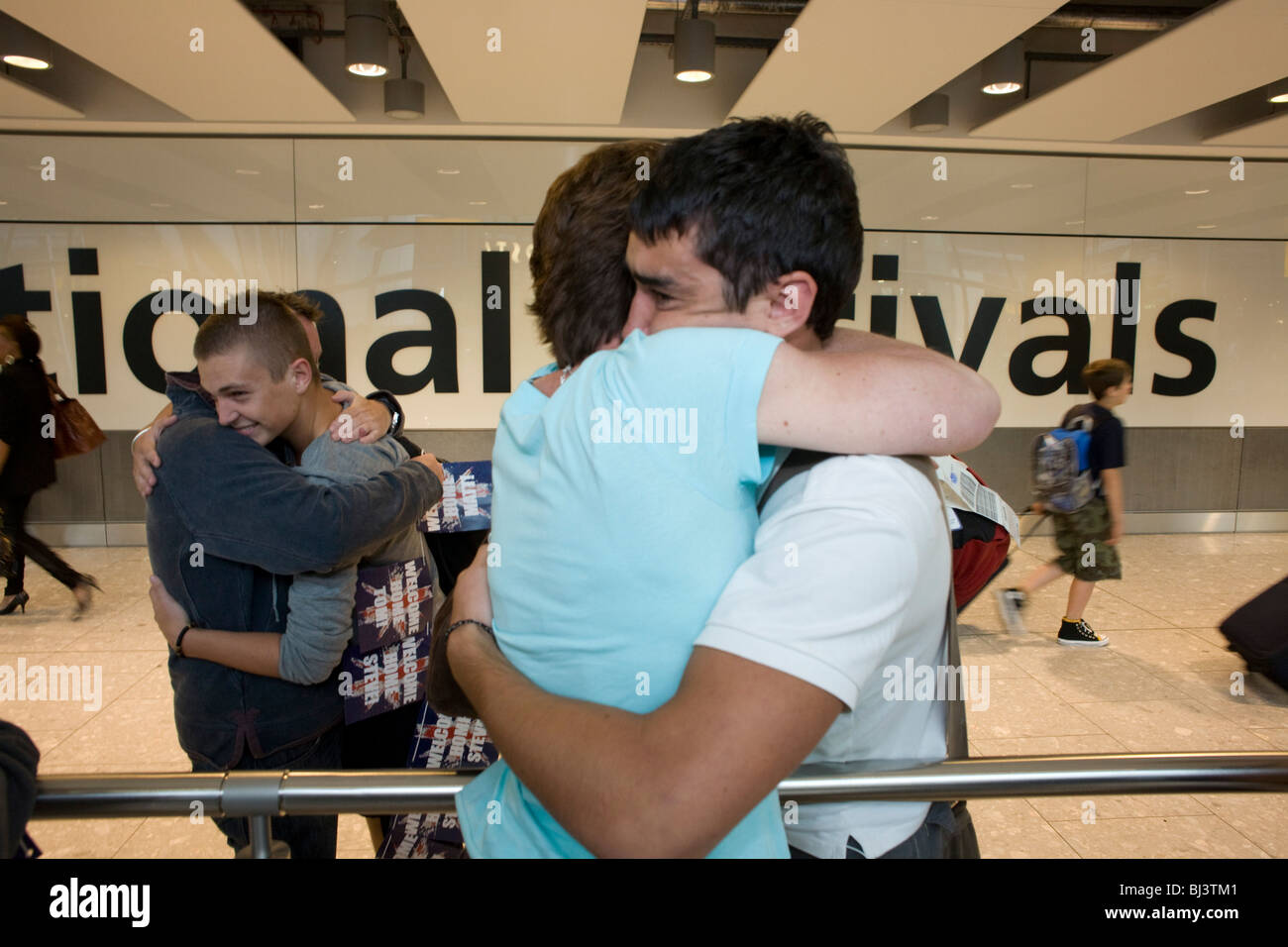 Mütter und Söhne umarmen emotional in der internationalen Ankünfte Hall von Heathrow Airport Terminal Stockbild