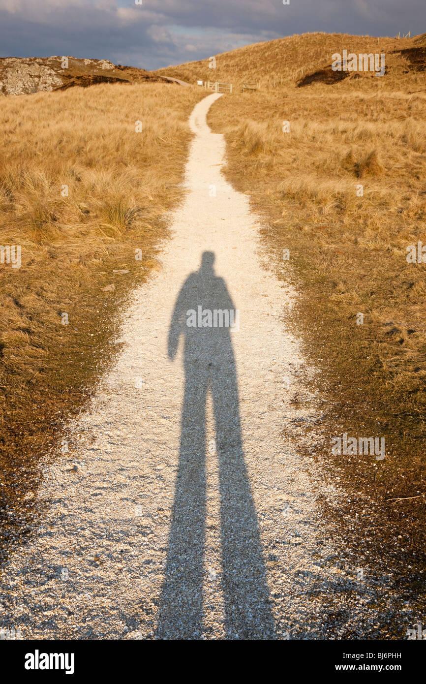 Der lange Schatten einer Person auf einen Pfad in der Abendsonne. Großbritannien Großbritannien Stockbild