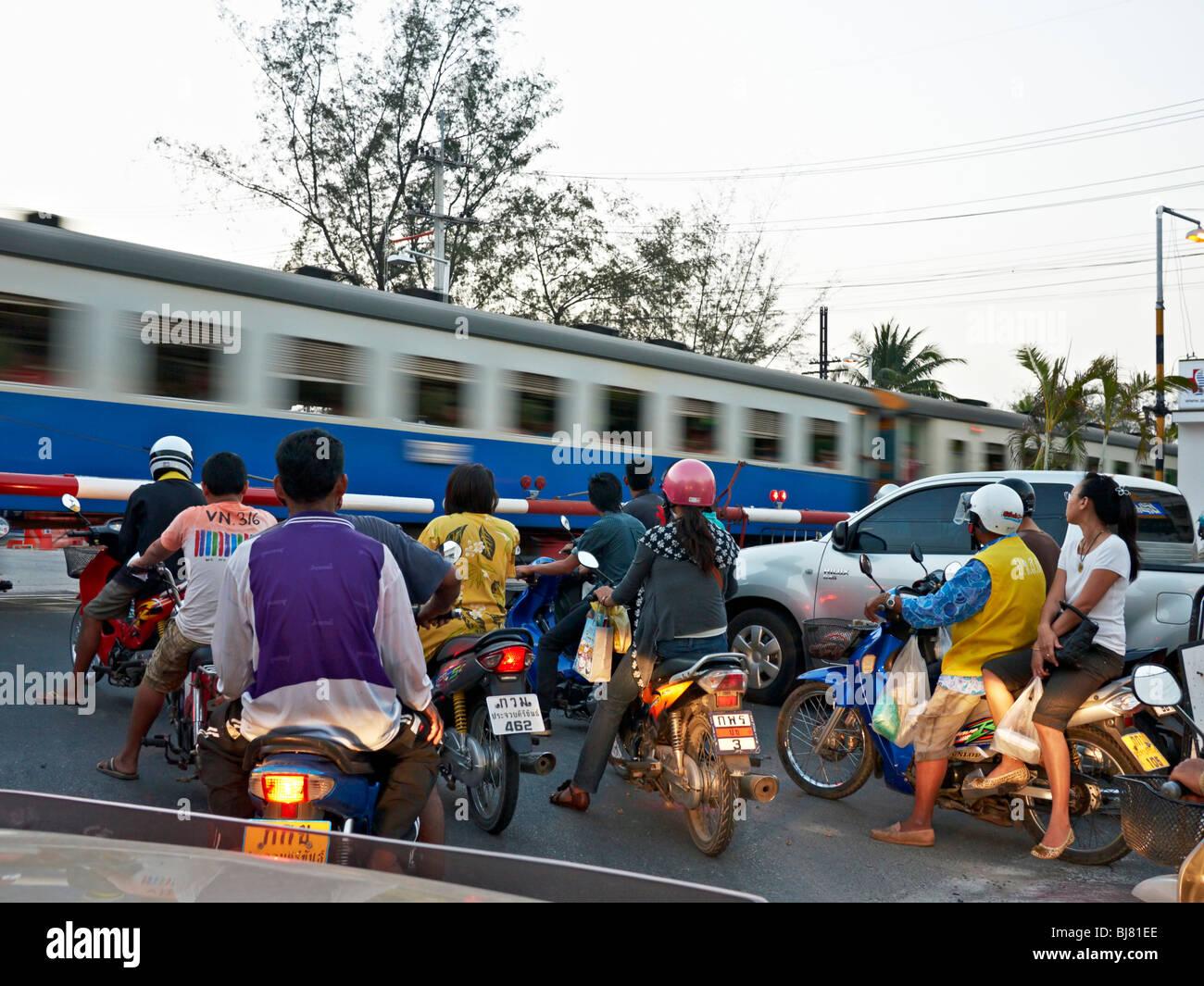 Zug auf Kreuzung mit Menschen als einem rasenden Zug warten geht. Hua Hin Thailand S. E. Asien Stockbild