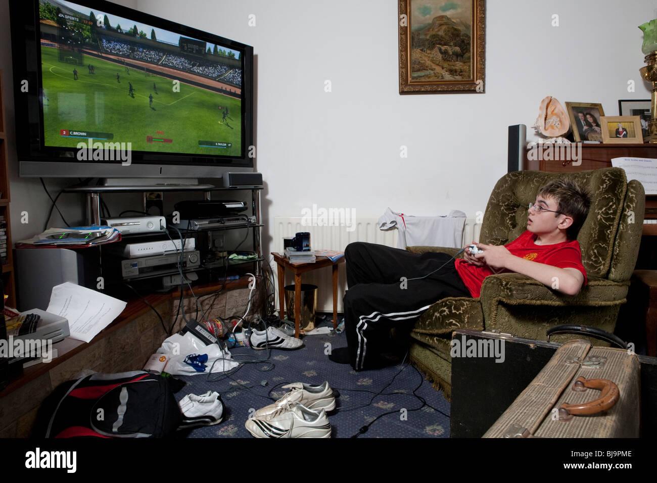 Jungen spielen Videospiel in unübersichtlichen Wohnzimmer Stockfoto
