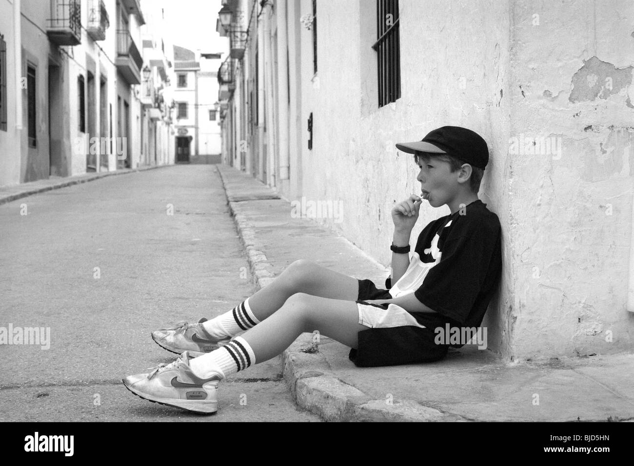 Kleiner Junge mit Baseballmütze saugen Lollipop in Javea, Spanien Stockbild