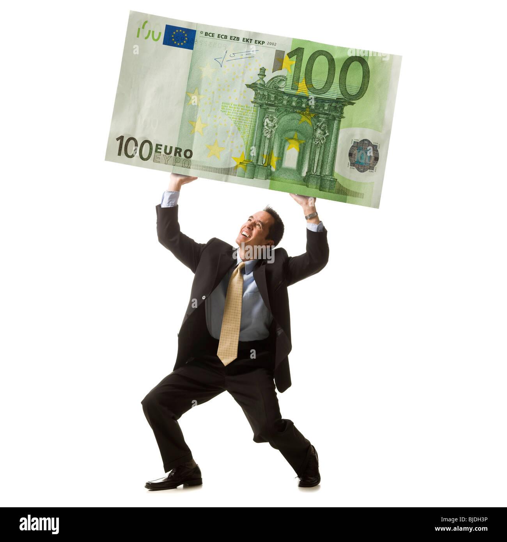 Unternehmer, die eine Banknote hochhalten Stockbild