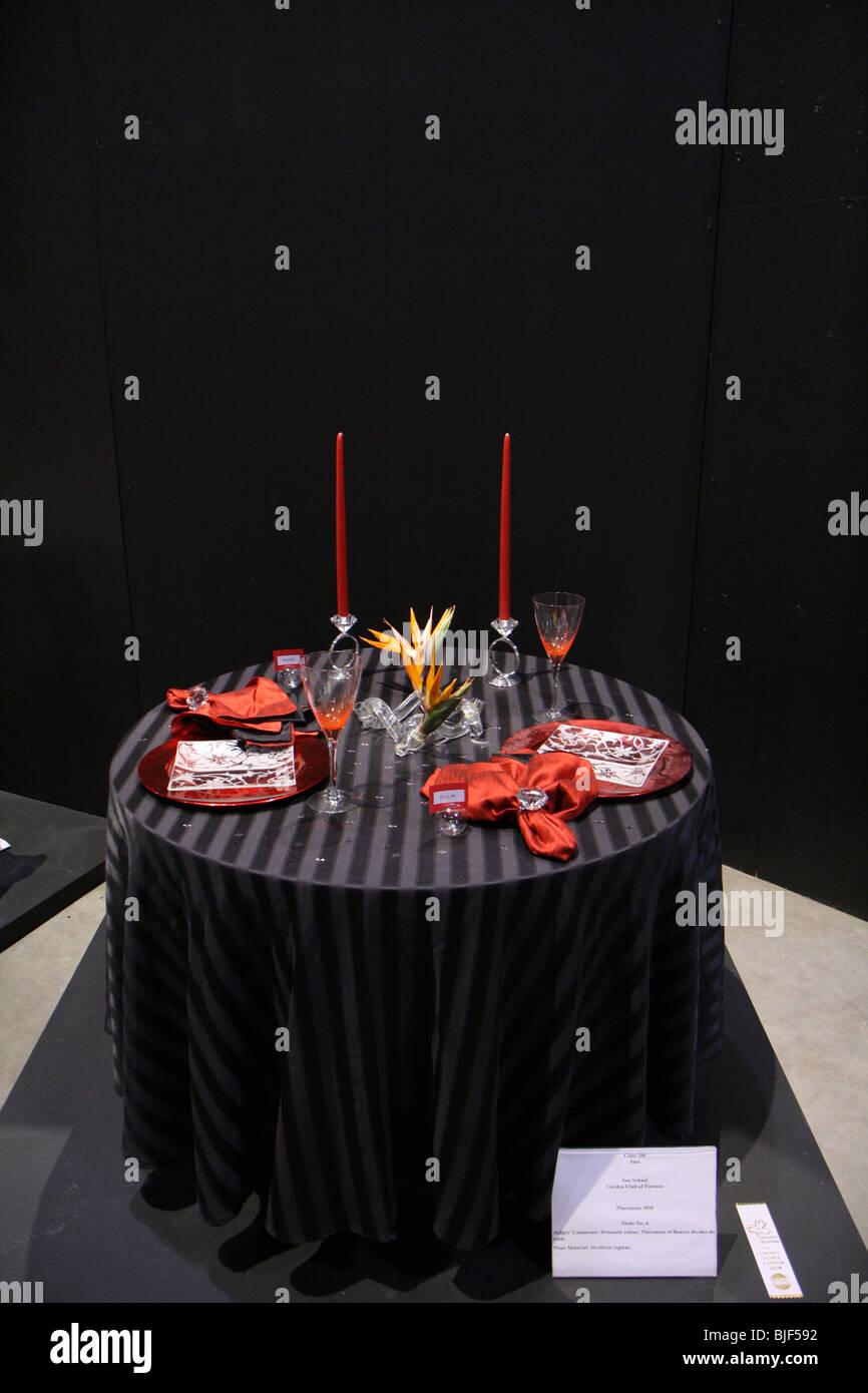 Eleganz Luxus Kerze Besteck Serviette Tafelglas Abendessen rose Vase Dekoration schwarz dunkel rot leuchtende Blume Stockbild