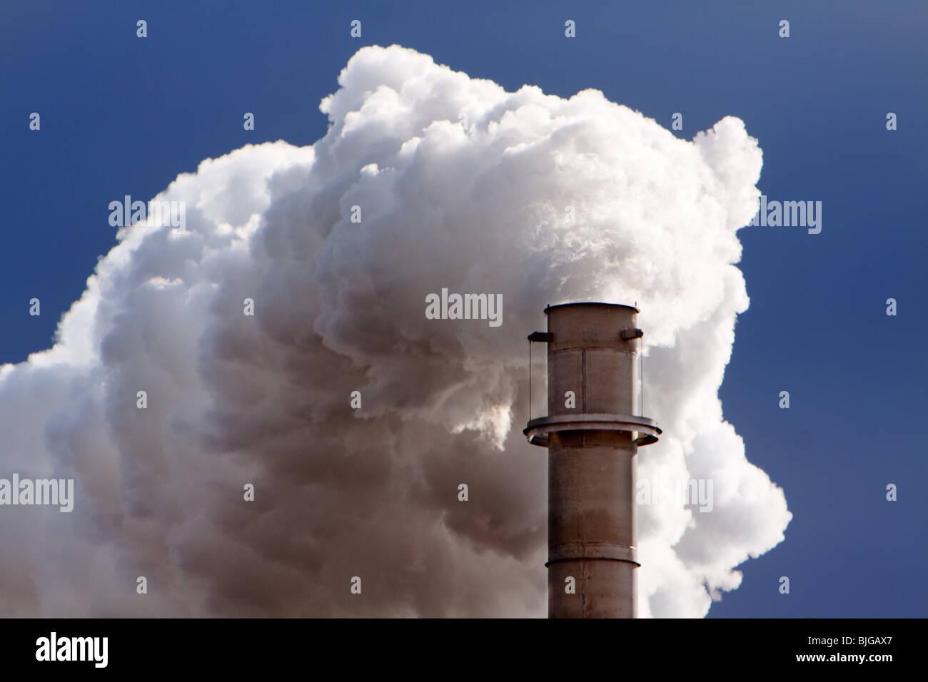 Ein Schornstein wabert Rauch und Dampf im ländlichen Nebraska. Schuss aus öffentlichen Straßen. Stockbild