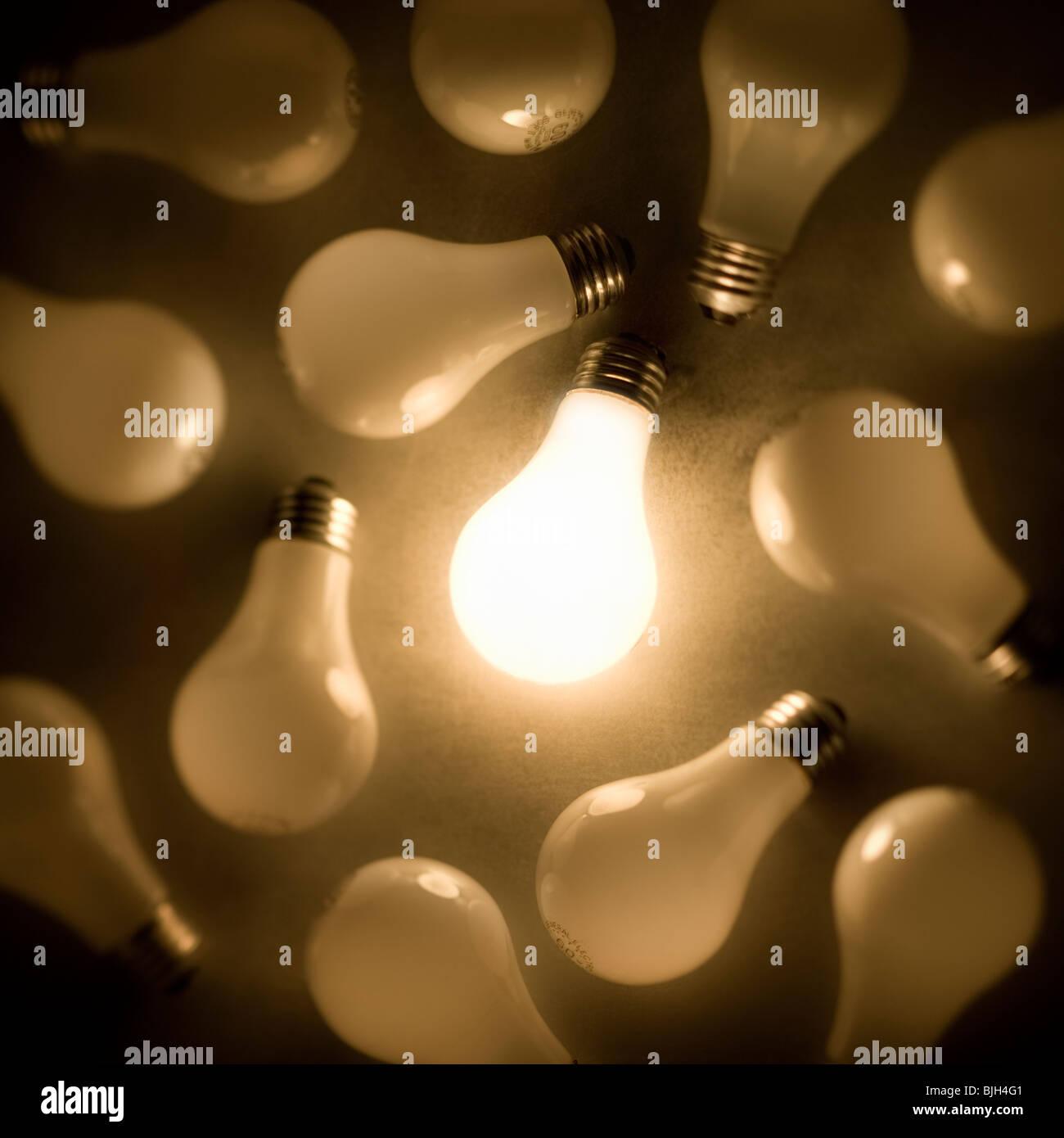 eine Glühbirne leuchtet unter vielen Stockbild
