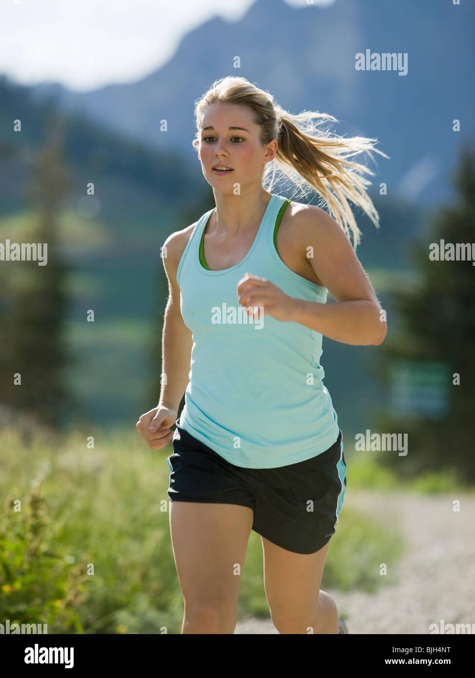 junge Frau läuft auf einem Bergweg Stockbild