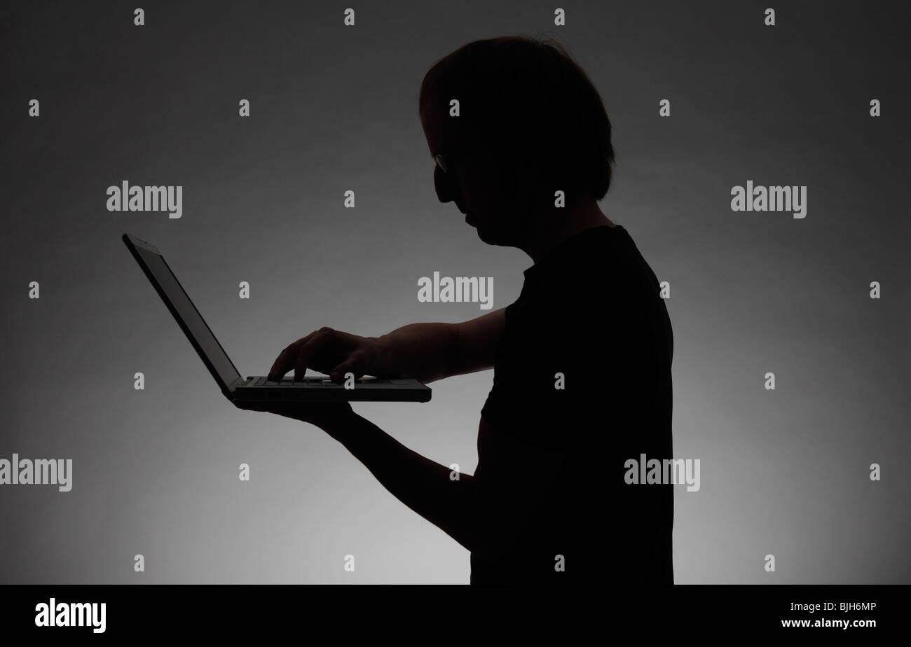 Mann mit einem Notebook. Symbol: Datendiebstahl, Cyber-Kriminalität usw. Stockbild