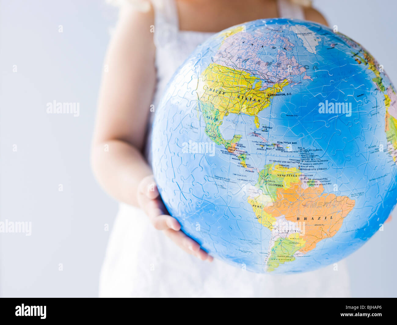 kleines Mädchen hält einen Globus Stockbild