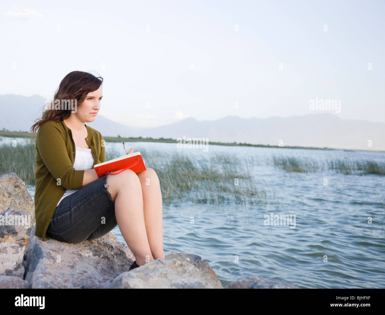 Frau sitzt an einem See in ein Tagebuch schreiben Stockbild