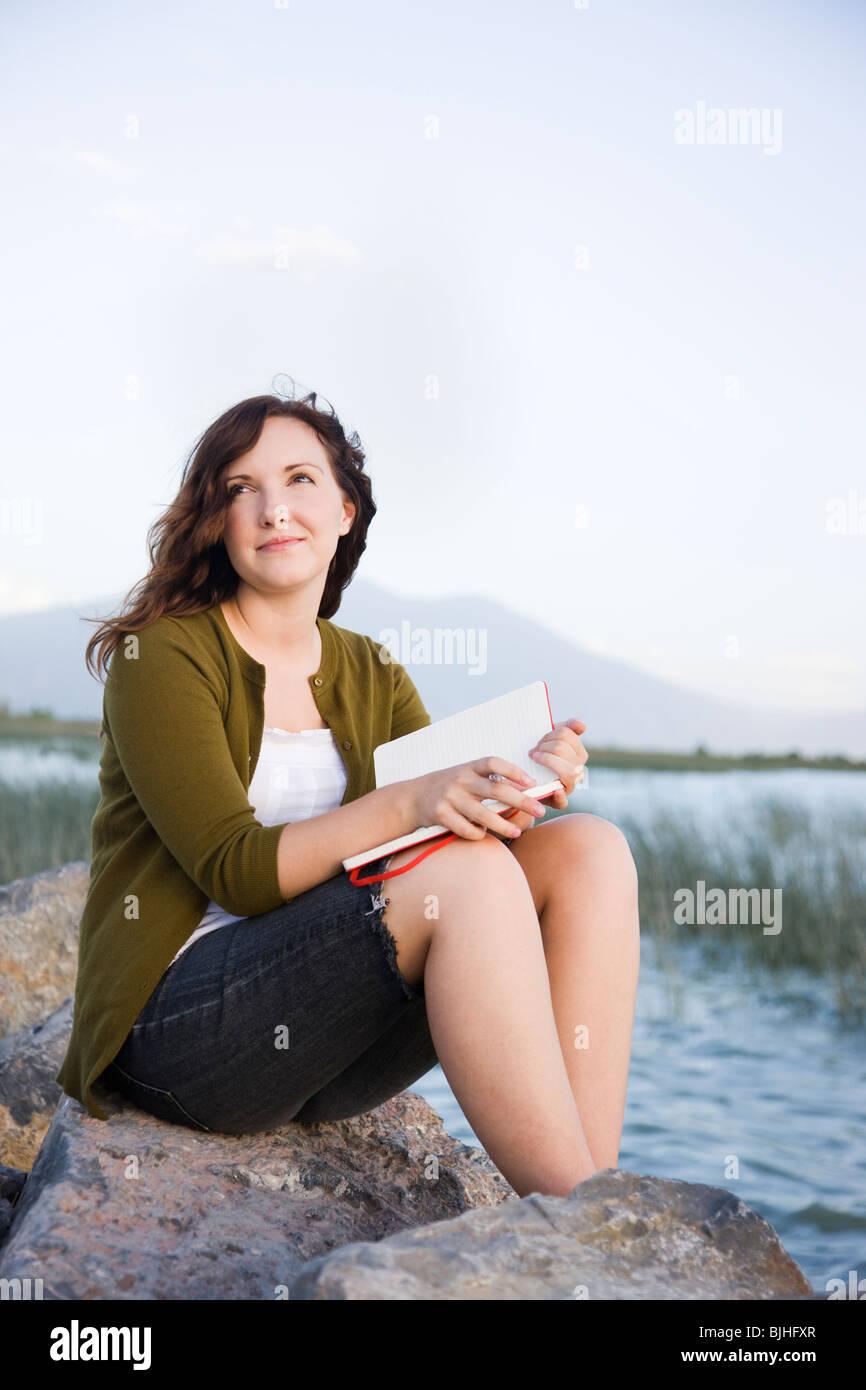 Frau sitzt an einem See mit einem notebook Stockbild