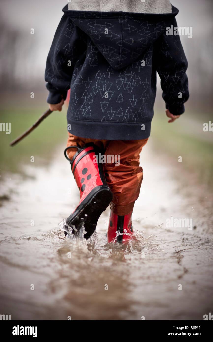 Jungen tragen Gummistiefel geht durch eine Wasserpfütze. Stockbild