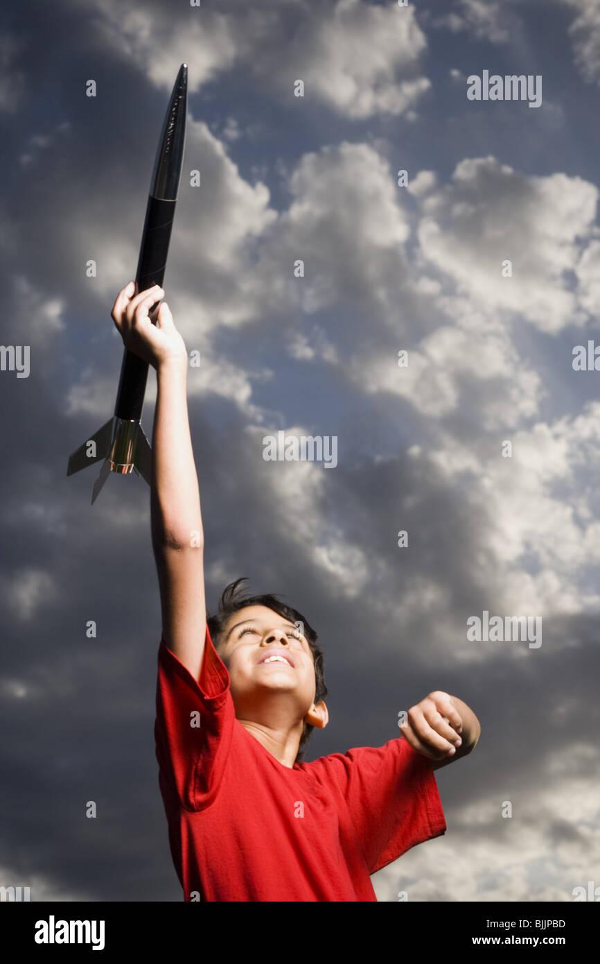 Jungen spielen mit Spielzeug Rakete im Freien am bewölkten Tag niedrigen Winkel Ansicht Stockbild
