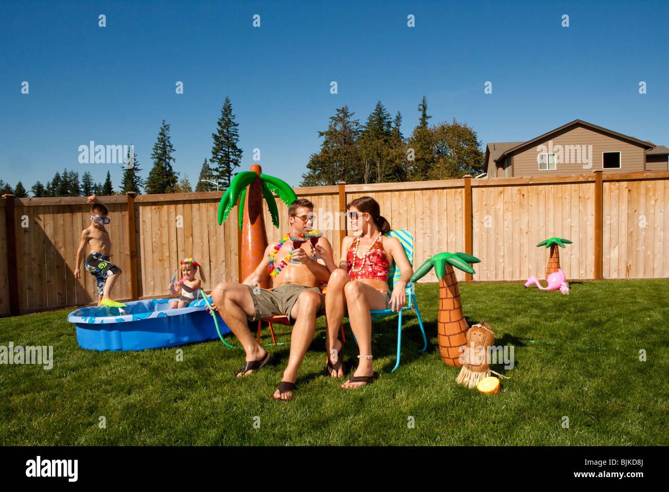 Familie im Hof mit Kinderbecken und cocktails Stockfoto