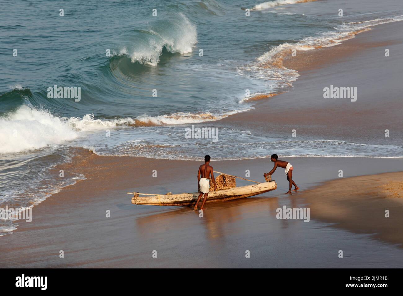 Zwei einheimische mit einem einfachen Angeln Boot am Strand südlich von Kovalam, Kerala, südlichen Malabarküste, Stockbild