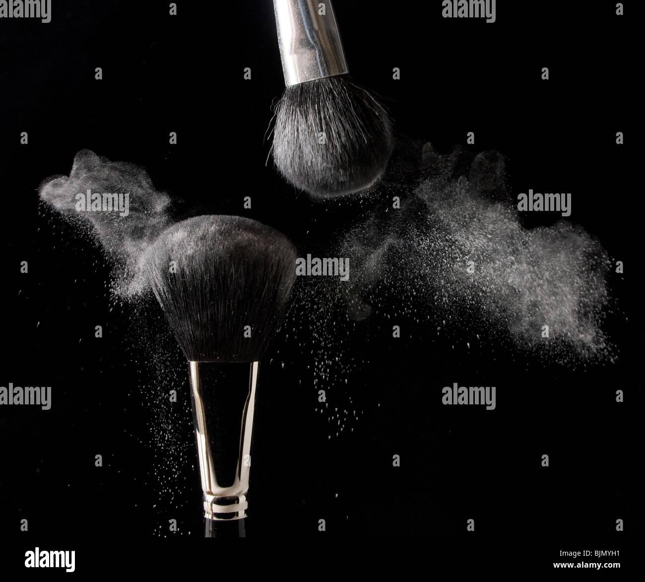 Pulver wird über einem schwarzen Hintergrund aus zwei Kosmetik Pinsel eingerieben. Stockbild