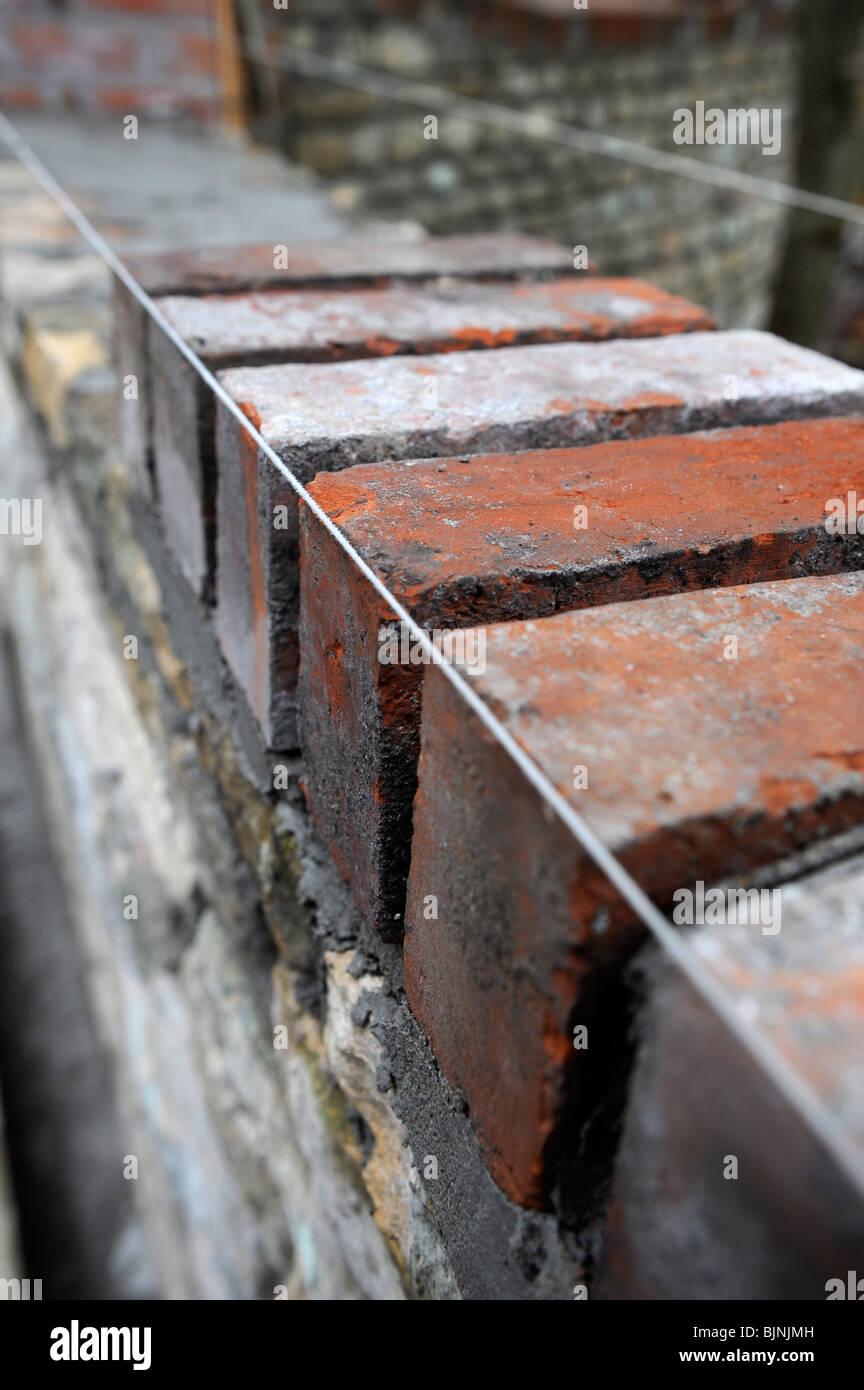 Bau einer Gartenmauer mit Cotswold Stone und aufgearbeiteten roten Ziegeln UK Stockbild