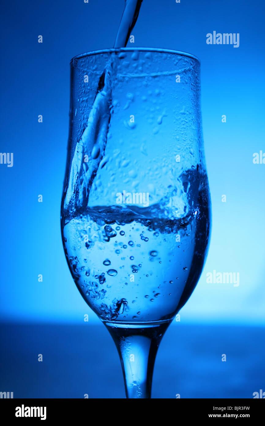 Glas mit Wasser auf blauem Hintergrund. Stockbild