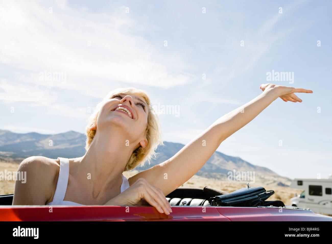 Frau in einem roten Cabrio Stockbild