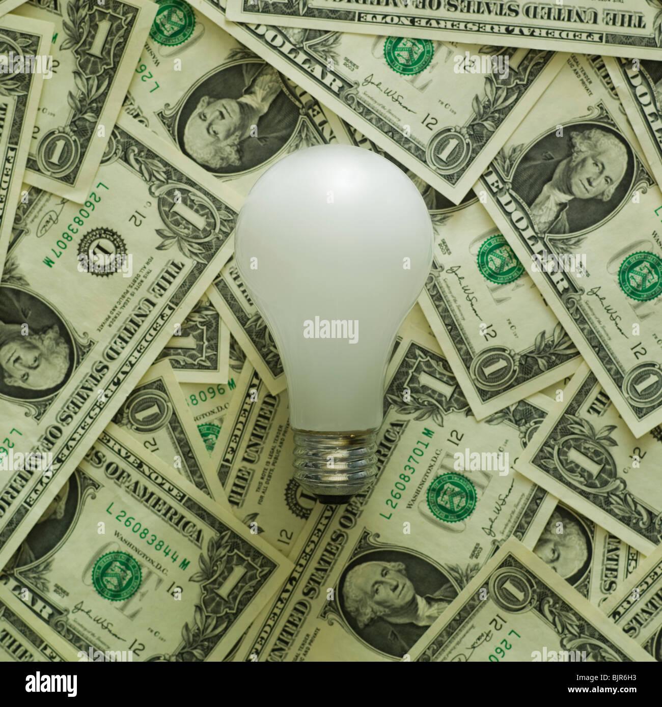 Glühbirne auf einen Haufen von Dollarnoten Stockbild