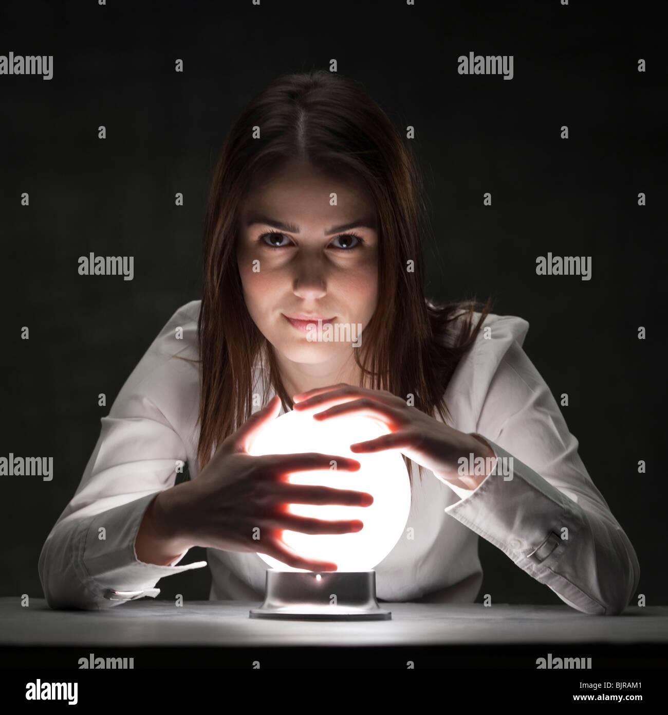 Studio-Porträt der jungen Frau, die mit Crystal ball Stockbild