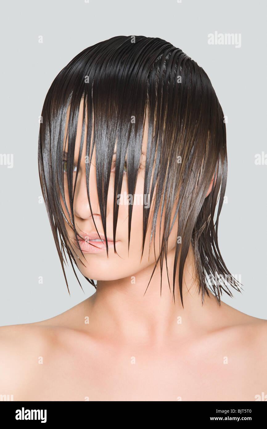 Eine Frau mit nassen Haaren bedeckte ihr Gesicht Stockbild