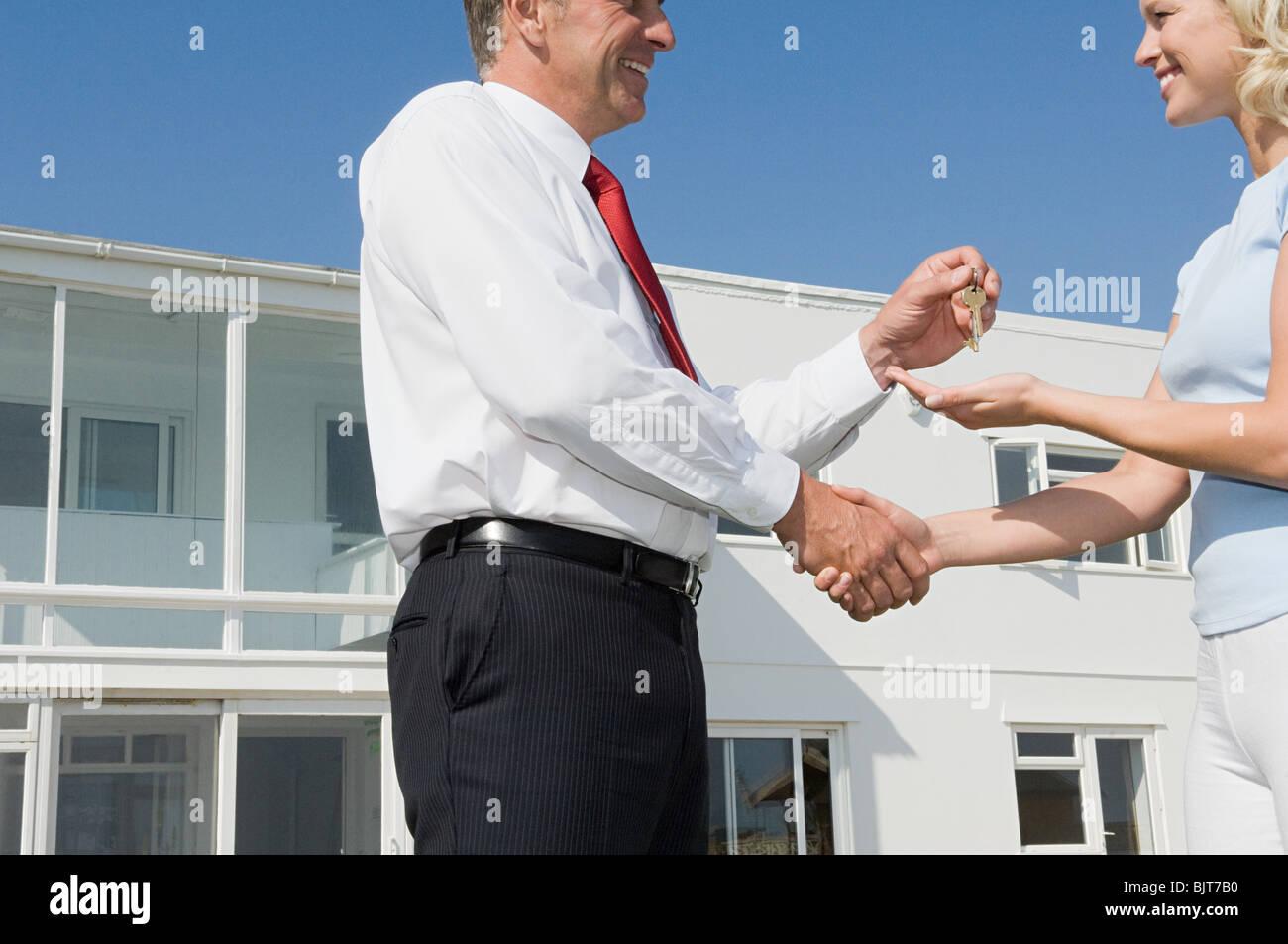Frau und Immobilienmakler Händeschütteln Stockbild
