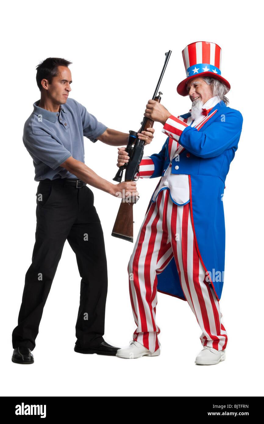 Mann in Uncle Sam Kostüm Beschlagnahme Pistole von anderen Menschen, Studio gedreht Stockbild