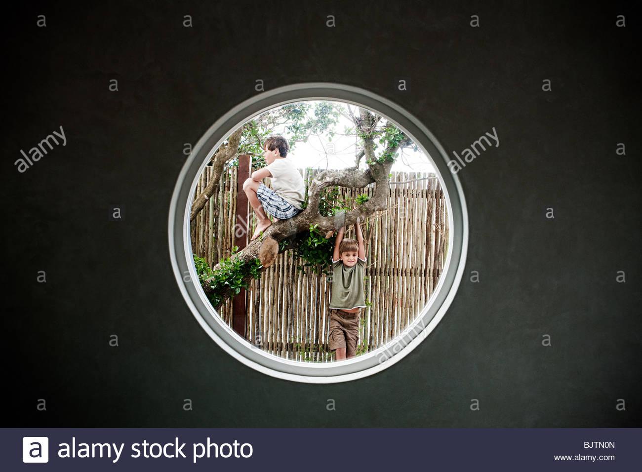 Jungen am Baum gesehen durch Kreis in Wand Stockbild