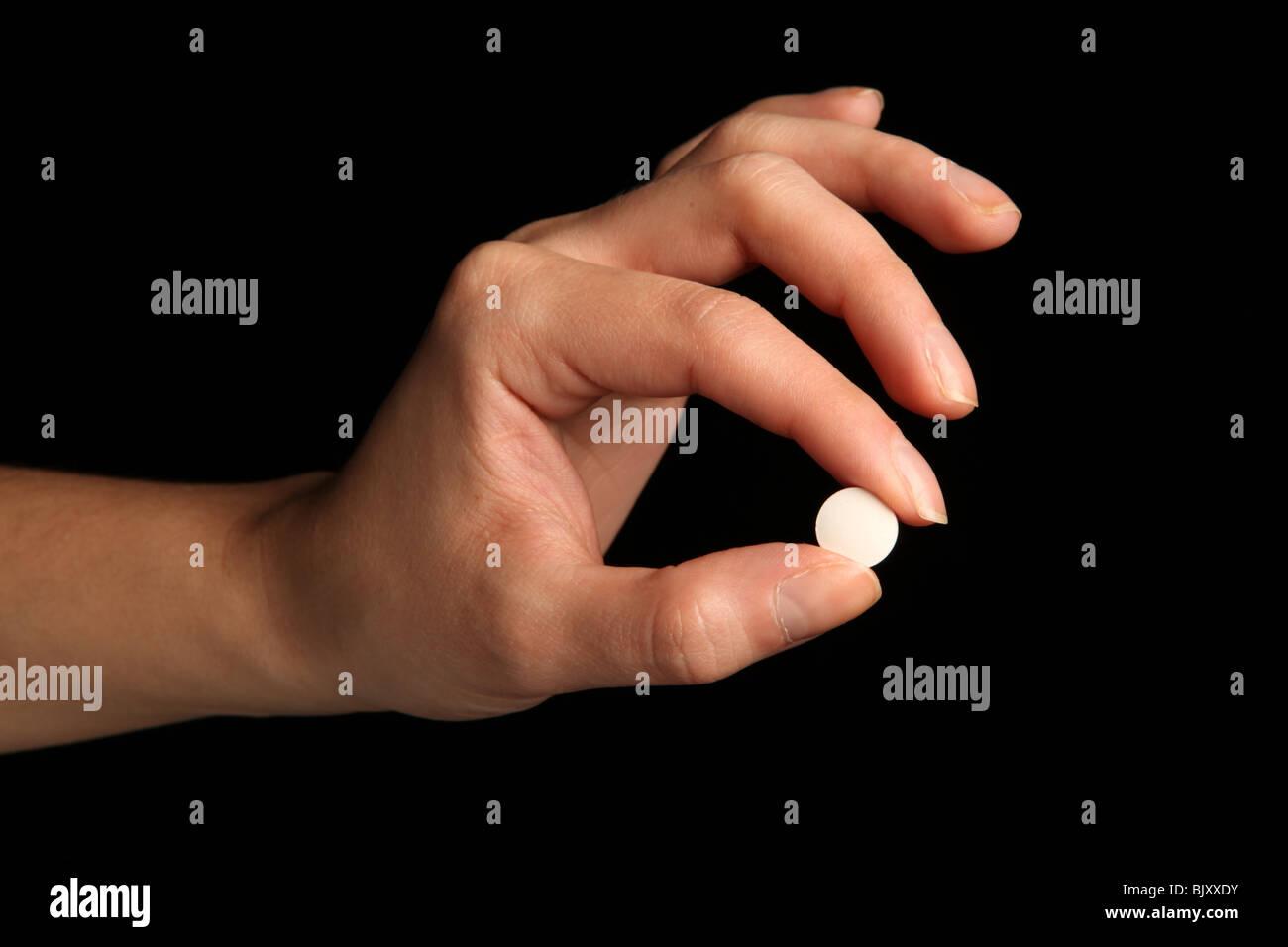 Eine weibliche Hand eine kleine weiße Pille zwischen den Fingern Stockbild