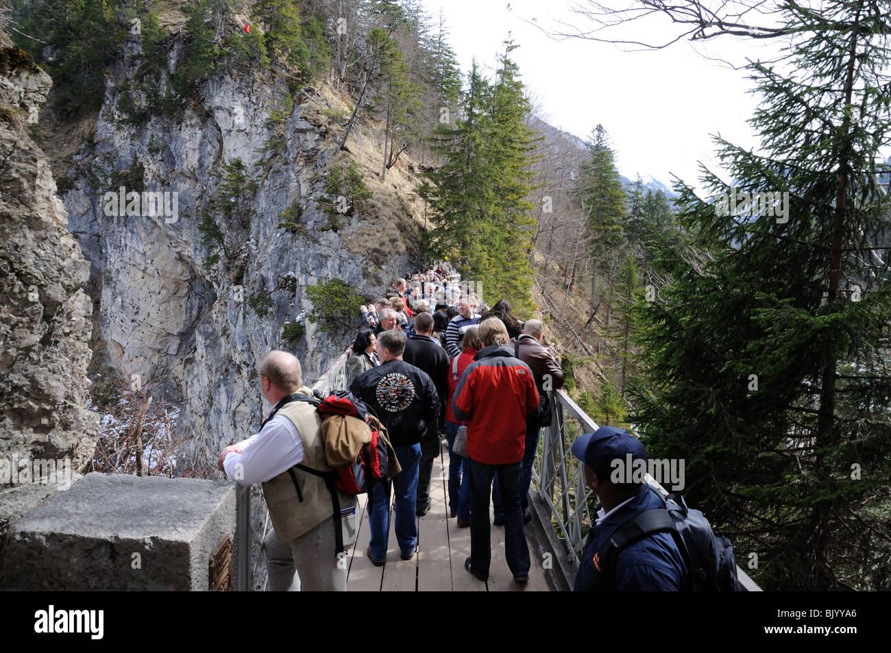 Touristen, die gerade Schloss Neuschwanstein von der Marien-Brücke. Bayern, Deutschland Stockbild