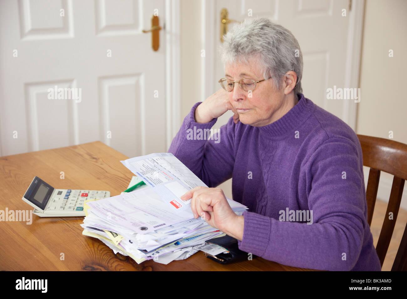 Ältere Frau Rentner mit einem großen Haufen von Rechnungen auf dem Tisch sucht eine große Gas-Tankrechnung Stockbild