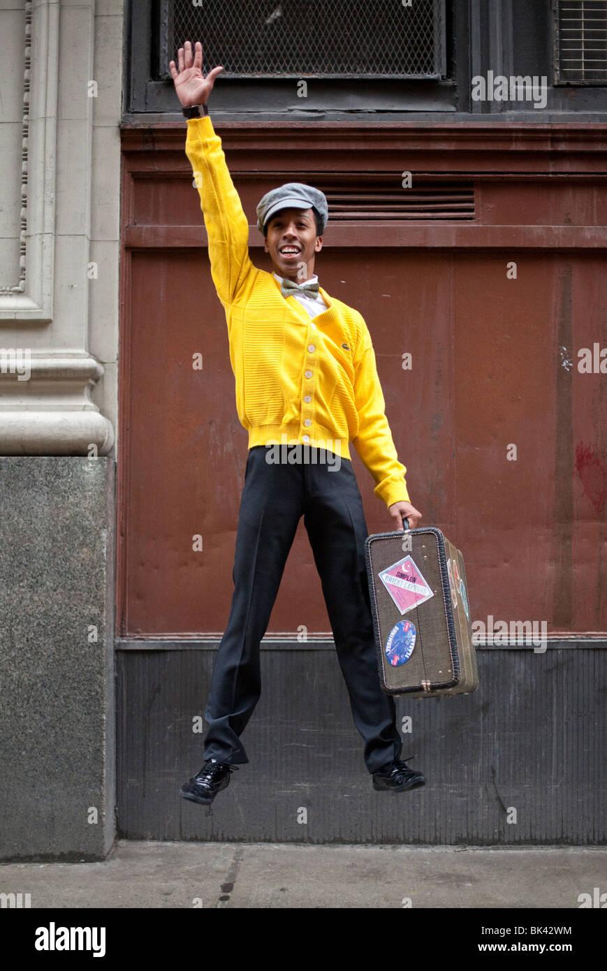 Ein Model-Release Porträt von einem hip, stylish, junge afroamerikanische Mann springt mit einem Retro-Koffer in Stockfoto