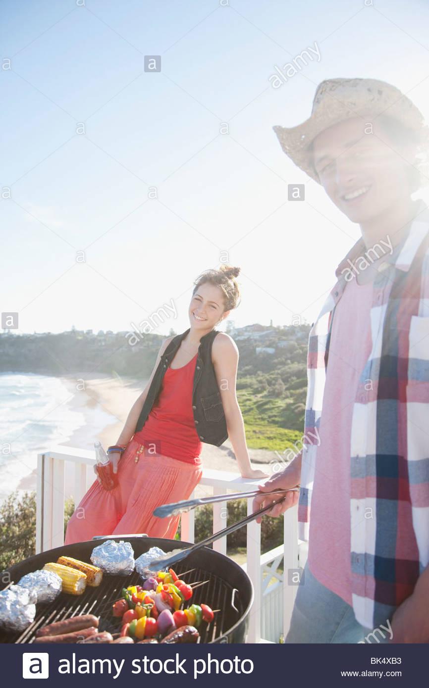 Mann und Frau tendenziell Grill mit Meer im Hintergrund Stockbild