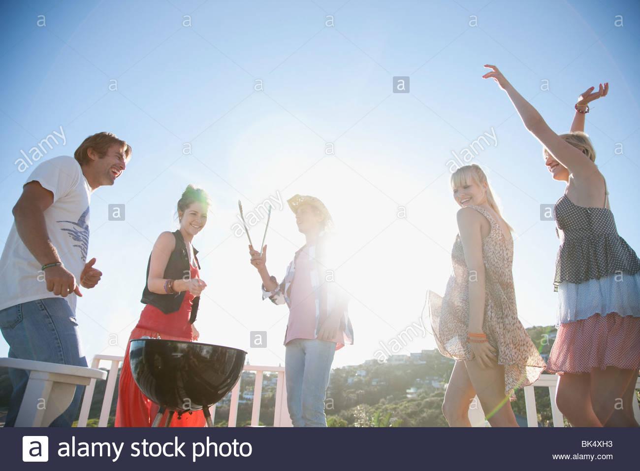 Freunde, tanzen und Grillen Stockbild