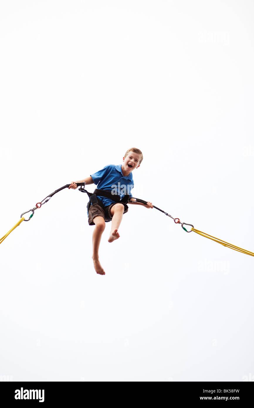 Junge mit Bungie Seil in der Luft Stockbild