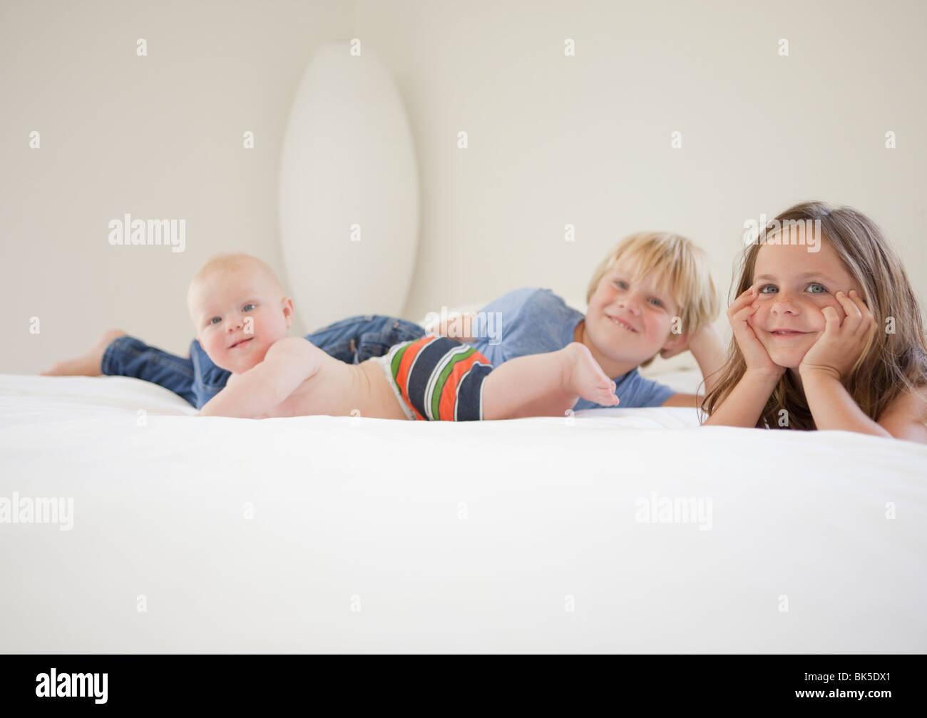 Geschwister, Faulenzen am weißen Bett Stockbild