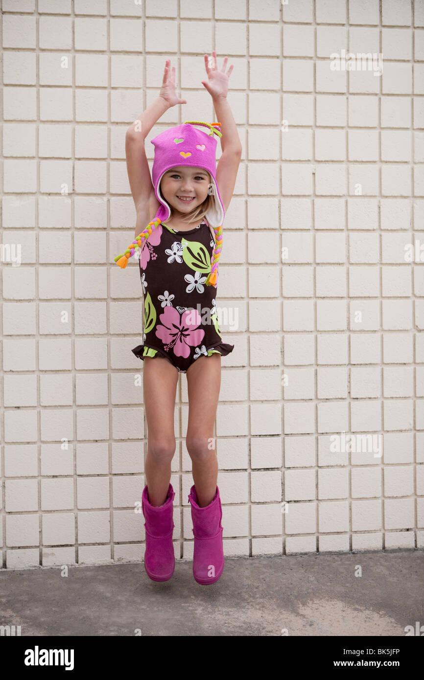 Mädchen im floralen Badeanzug springen Stockbild